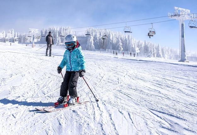 Mała dziewczynka uczy się jeździć na nartach w górskim kurorcie z wyciągiem narciarskim