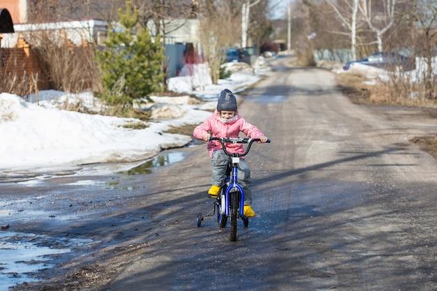 Mała dziewczynka uczy się jeździć na rowerze z bezpiecznymi kołami na drodze w wiosce, gdy jeszcze nie stopił się cały śnieg