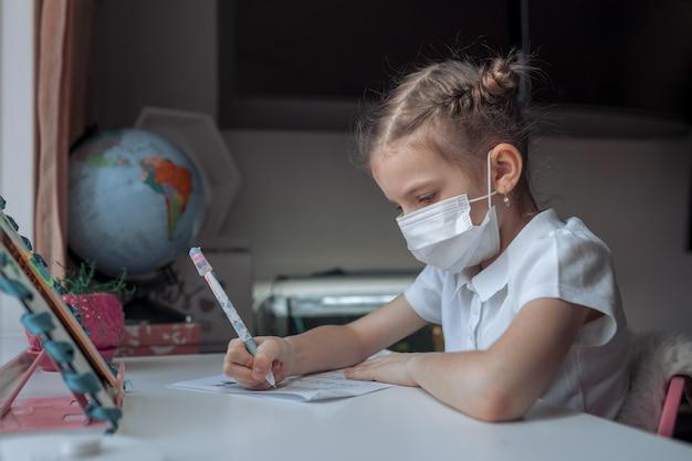 Mała dziewczynka uczy się medyczną maskę przy odległości domowym szkoleniem