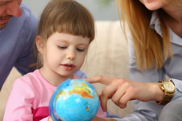 Mała dziewczynka uczy się o nawigaci i trasach trzyma kulę ziemską w rękach