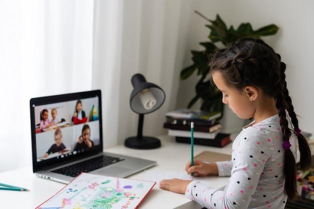 Mała dziewczynka uczy się online przy użyciu laptopa w domu