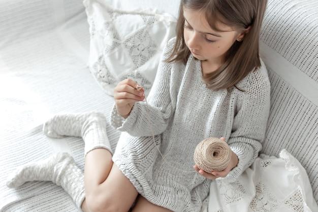Mała dziewczynka uczy się robić na drutach, domowy wypoczynek i robótki ręczne.