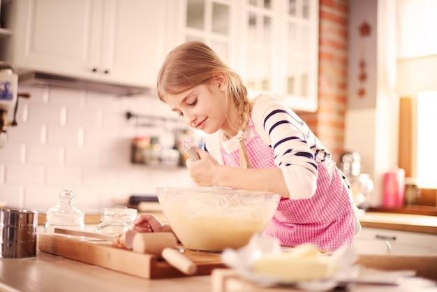 Mała dziewczynka uczy się robić właściwe ciastod