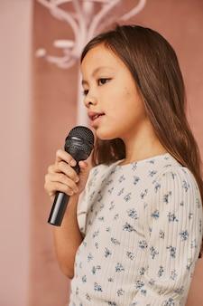 Mała dziewczynka uczy się śpiewać w domu z mikrofonem