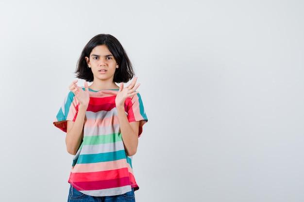 Mała dziewczynka udaje, że łapie coś w t-shirt i wygląda na zdezorientowaną. przedni widok.