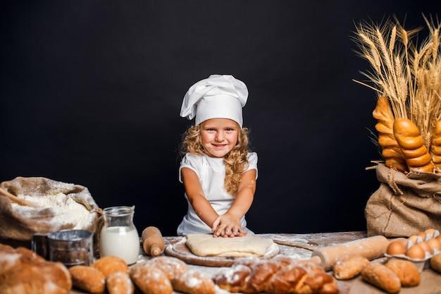 Mała dziewczynka ugniata ciasto przy stołem