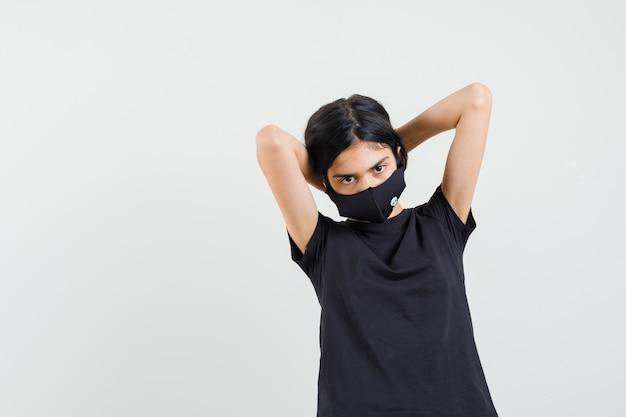 Mała dziewczynka układa włosy w czarną koszulkę, widok z przodu maski.