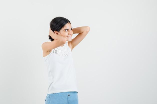 Mała dziewczynka układa włosy za głową w białą bluzkę, szorty i wygląda wesoło. przedni widok.