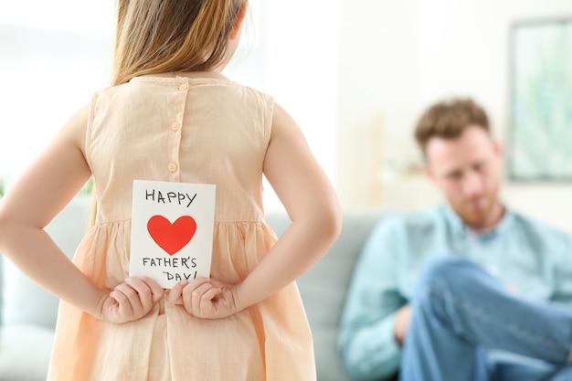 Mała dziewczynka ukrywa kartkę z życzeniami dla swojego ojca za plecami