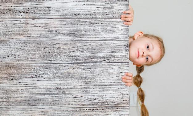 Mała dziewczynka ukrywa się za drewnianą deską i patrzy uważnie. .