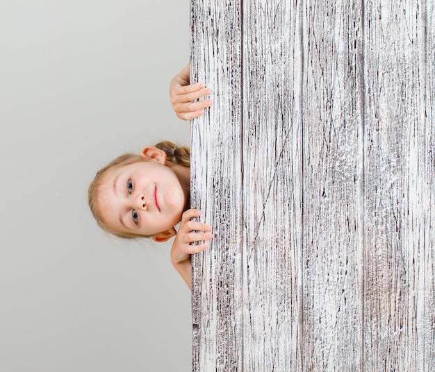 Mała dziewczynka ukrywa się za drewnianą deską i wygląda pewnie.