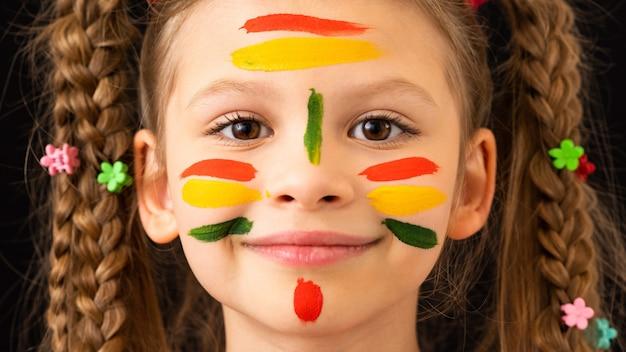 Mała dziewczynka umazała sobie ręce i twarz farbą.