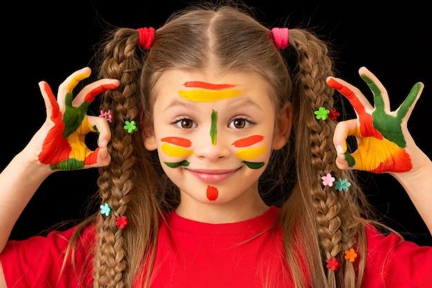 Mała dziewczynka umazana farbą pozuje.