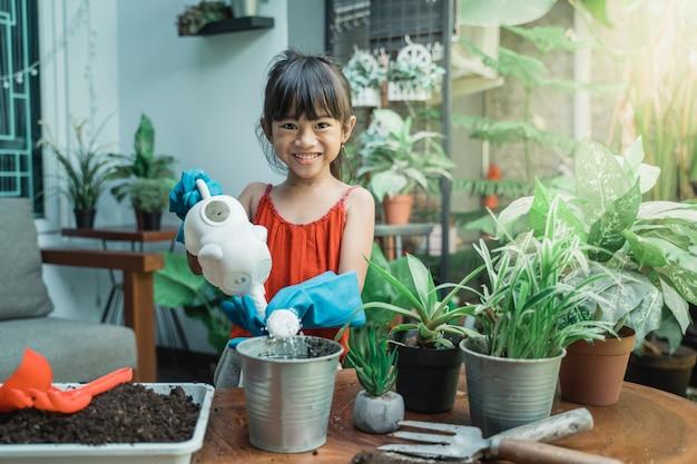Mała dziewczynka uprawia ogródek w domu