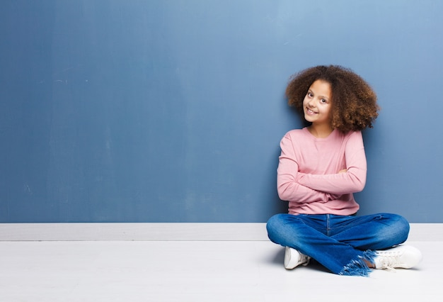 Mała dziewczynka uśmiecha się do kamery ze skrzyżowanymi rękami i szczęśliwy, pewny siebie, zadowolony wyraz twarzy, widok z boku siedzi na podłodze