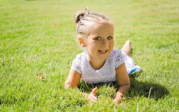 Mała dziewczynka uśmiecha się figlarnie leżąc na trawie.
