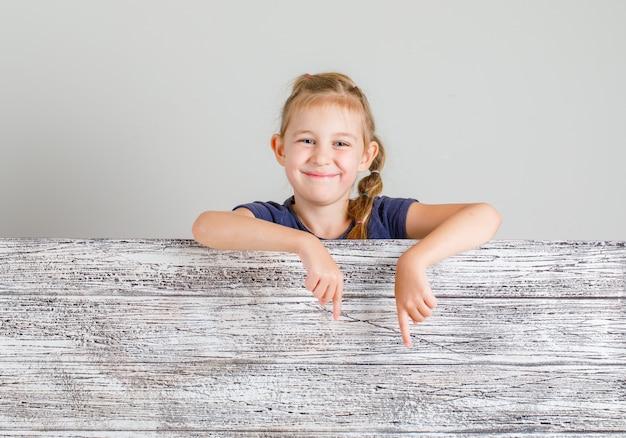 Mała dziewczynka uśmiecha się i gestykuluje poniżej w koszulce, widok z przodu.