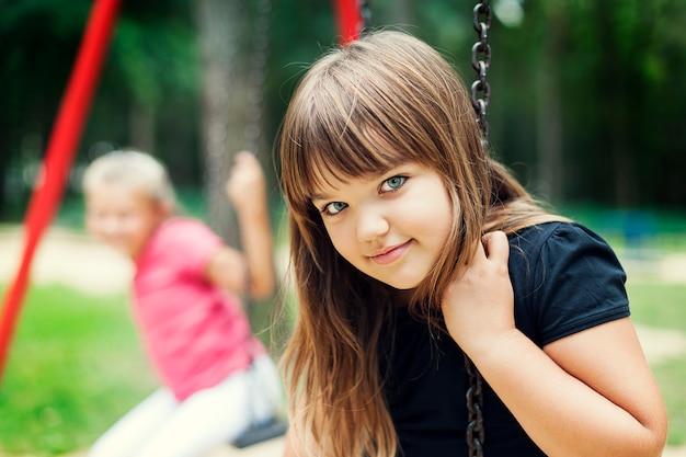 Mała dziewczynka uśmiecha się na huśtawce