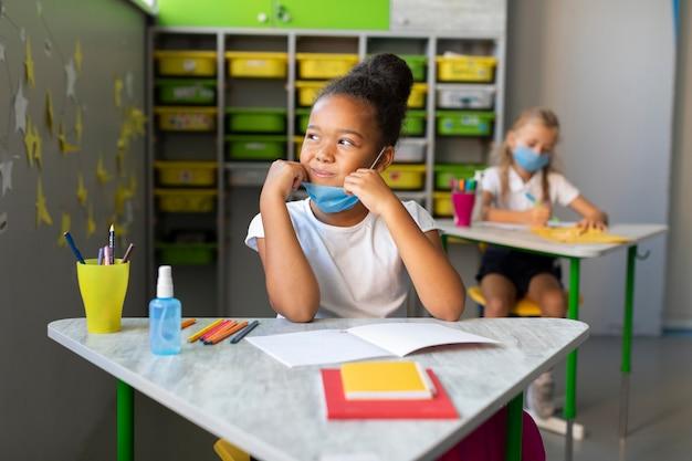 Mała dziewczynka uśmiecha się, patrząc w okno w klasie