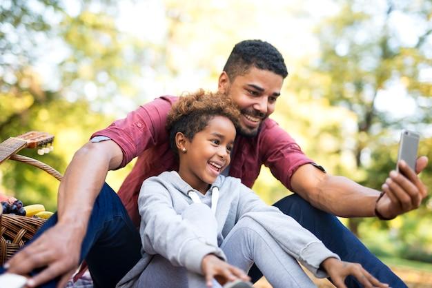 Mała dziewczynka uśmiecha się podczas gdy ojciec bierze selfie