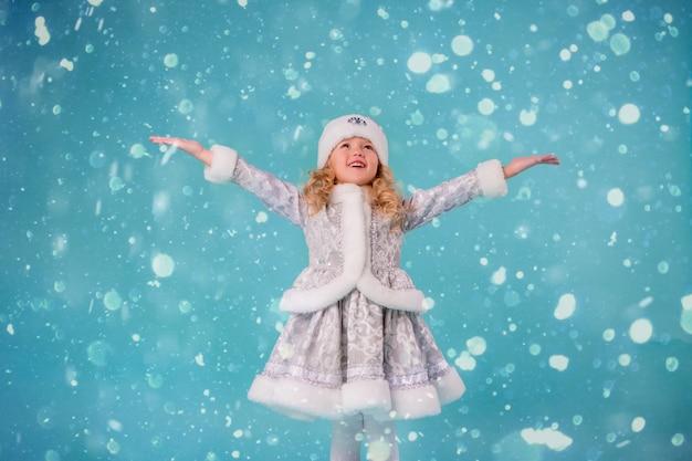 Mała dziewczynka uśmiecha się w stroju dziewiczy śnieg