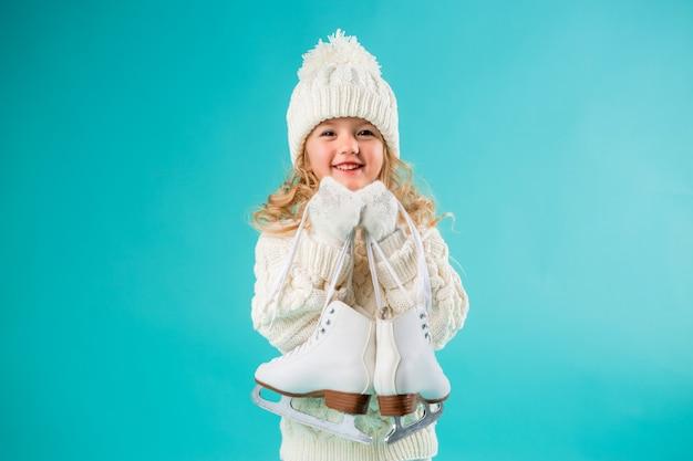 Mała dziewczynka uśmiecha się w zimowym białym kapeluszu i swetrze, trzymając łyżwy
