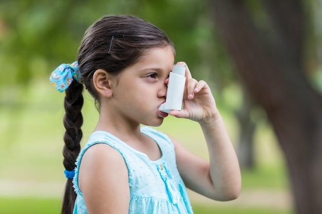 Mała dziewczynka używa jego inhalator