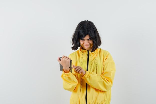 Mała dziewczynka używa kalkulatora w żółtej bluzie z kapturem i wygląda niepewnie. przedni widok.