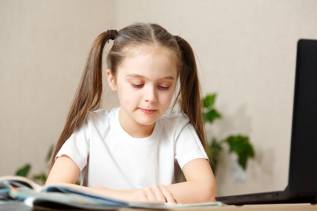 Mała dziewczynka używa laptopa do nauki w domu.