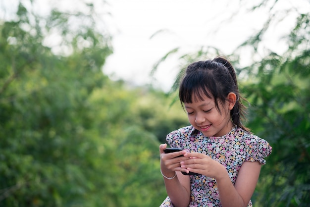 Mała dziewczynka używa mądrze telefon z uśmiechem