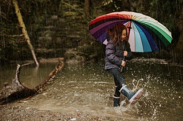 Mała dziewczynka używa parasola w strumieniu w deszczowy dzień