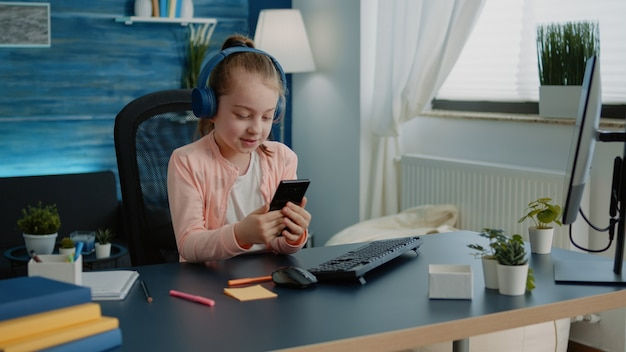 Mała dziewczynka używa smartfona do lekcji podczas rozmowy wideo