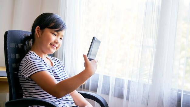 Mała dziewczynka używa smartphone dla rozmowy wideo