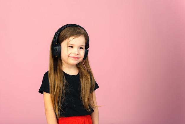 Mała dziewczynka w bezprzewodowych dużych czarnych słuchawkach na różowej pastelowej ścianie. pojęcie słuchania i cieszenia się muzyką. miejsce na tekst, miejsce