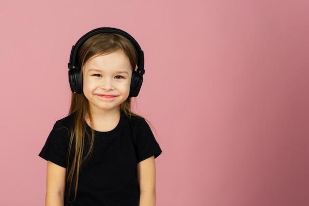 Mała dziewczynka w bezprzewodowych dużych czarnych słuchawkach. pojęcie słuchania i cieszenia się muzyką. miejsce na tekst, miejsce