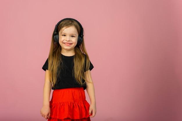 Mała dziewczynka w bezprzewodowych dużych czarnych słuchawkach uśmiecha się