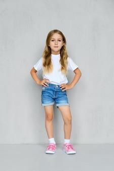Mała dziewczynka w białej koszulce, dżinsach i różowych trampkach stoi z ręką w kieszeni przy ścianie