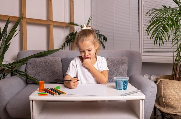 Mała dziewczynka w białej koszulce siedzi przy stole i rysuje ołówkiem