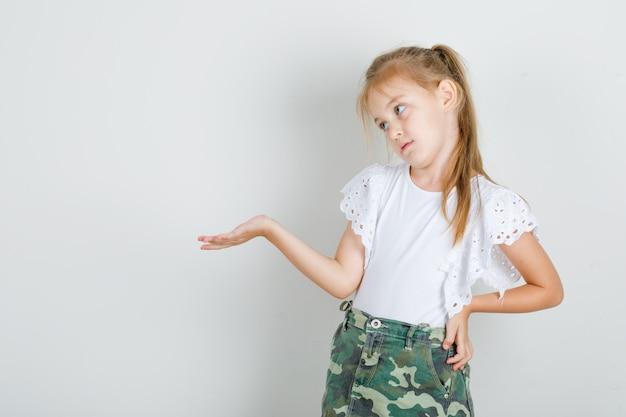 Mała dziewczynka w białej koszulce, spódnica z ręką na talii