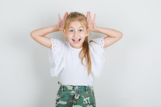 Mała dziewczynka w białej koszulce, spódnicy, gestykuluje rękami nad uszami i wygląda śmiesznie