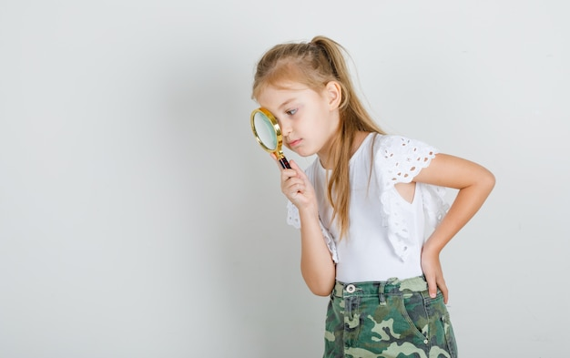Mała dziewczynka w białej koszulce, spódnicy patrząc przez szkło powiększające
