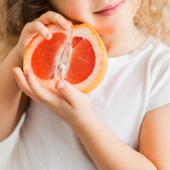 Mała dziewczynka w białej koszulce trzyma w rękach grejpfruta i uśmiecha się. zdjęcie pionowe
