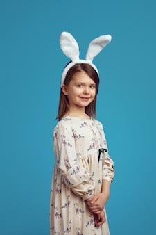 Mała dziewczynka w białej koszuli i uszach królika uśmiecha się nad niebieską ścianą