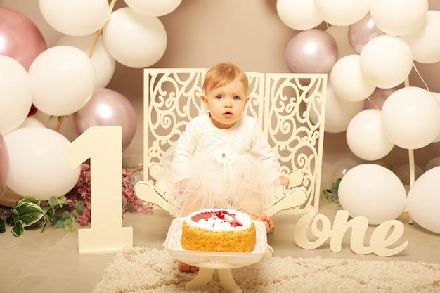 Mała dziewczynka w białej sukience siedząca na białej ławce urodziny numer jeden z balonami ciasto
