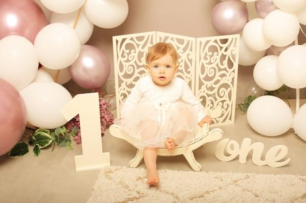 Mała dziewczynka w białej sukience siedząca na białej ławce urodziny numer jeden z balonami