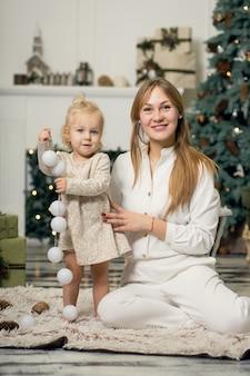 Mała dziewczynka w białej sukni siedzi z mamą.