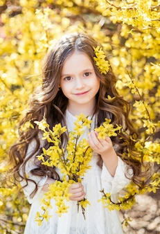 Mała dziewczynka w białej sukni z żółtymi kwiatami w dłoniach. dziecko na tle żółtych kwiatów. wiosenny portret dziecka.