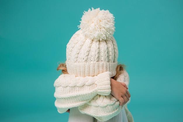Mała dziewczynka w białej zimowej czapka i sweter na niebiesko