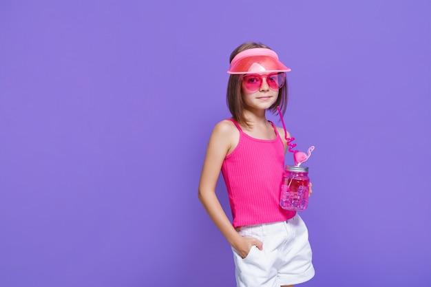 Mała dziewczynka w białych spodenkach, różowej koszulce, modnych okularach, z drinkiem w dłoni i letnim daszkiem