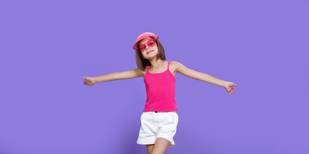 Mała dziewczynka w białych spodenkach, różowej koszulce, różowych modnych okularach i letnim daszku